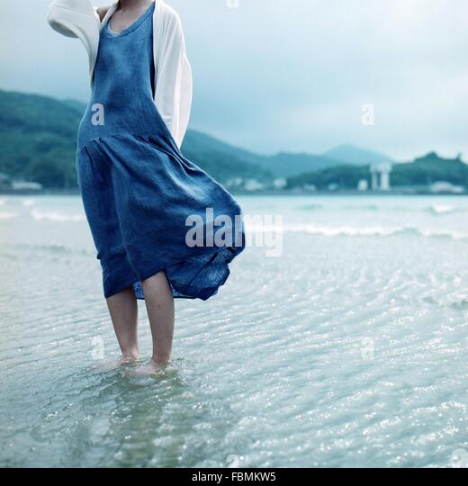 Low Section Of Woman Standing In Water By Shore - Stock Image