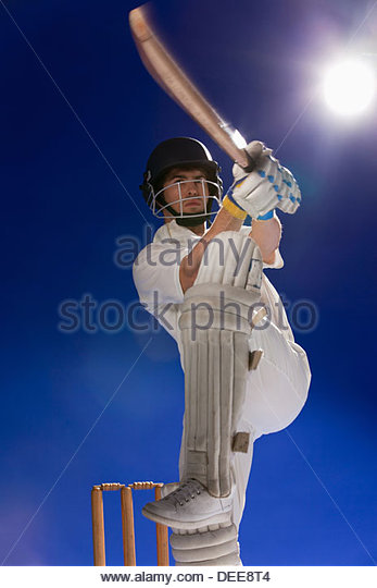 Cricket player swinging bat - Stock Image