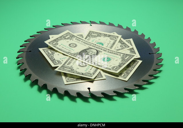 A sharp circular metal saw blade with US currency on green background. - Stock Image
