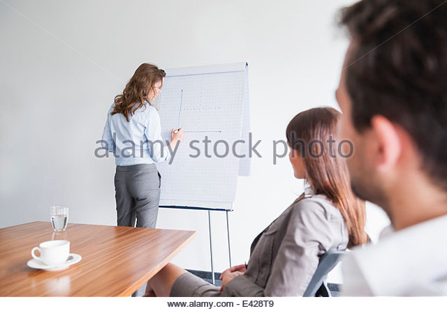 Woman drawing graph on flipchart - Stock-Bilder