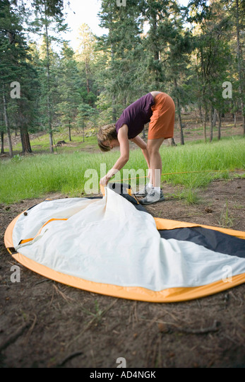 A woman setting up a tent - Stock-Bilder