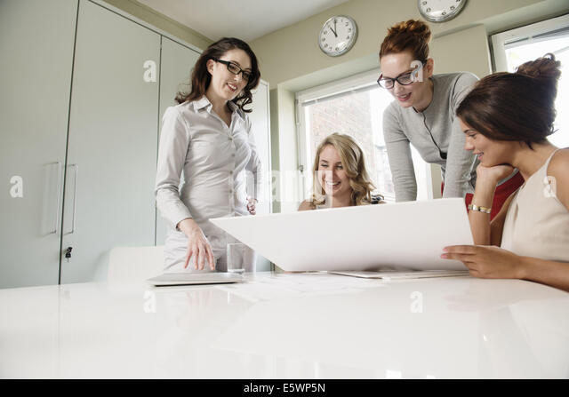 Four female designers looking at blueprint in office - Stock-Bilder