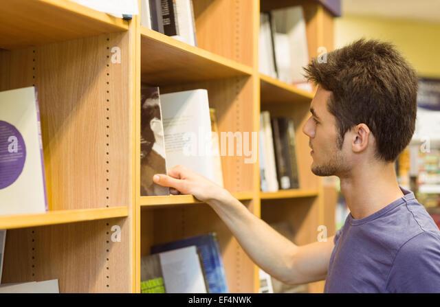 University student choosing books on bookshelves - Stock Image