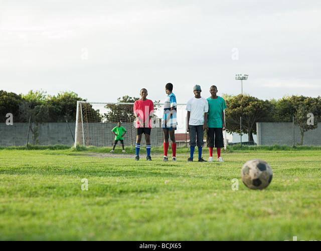Teenage boys playing football - Stock Image