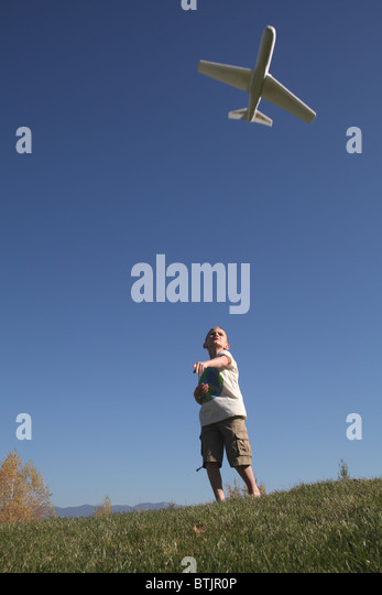young boy throwing toy airplane into the air - Stock Image