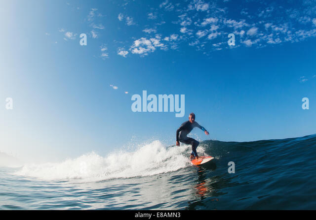 Mid adult man surfing wave, Leucadia, California, USA - Stock Image