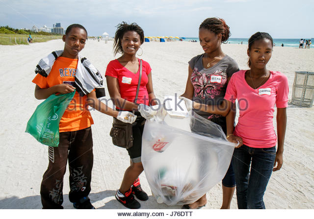 Miami Beach Florida Hands on Miami Beach Clean-up litter trash pollution environment sand volunteer student Black - Stock Image