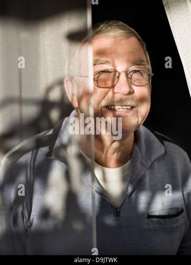 Senior man wearing glasses and smiling through sunlight curtain - Stock Image