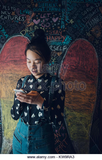 Asian tween girl texting with smart phone against wall with chalk angel wings - Stock Image