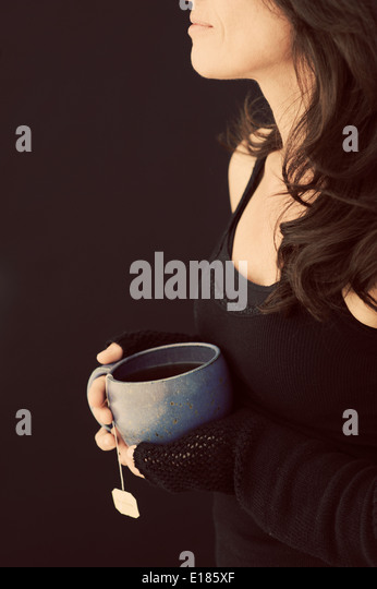 Woman holding cup of tea. - Stock Image