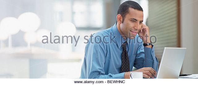 Businessman using laptop in office - Stock-Bilder