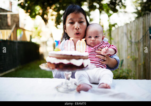 Mother holding baby son, blowing out candles on cake - Stock Image