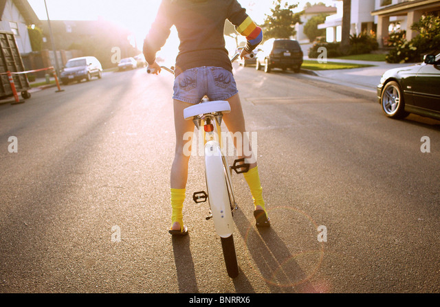 Young woman wearing yellow socks and a hoodie prepares to start riding a cruiser bike. - Stock-Bilder