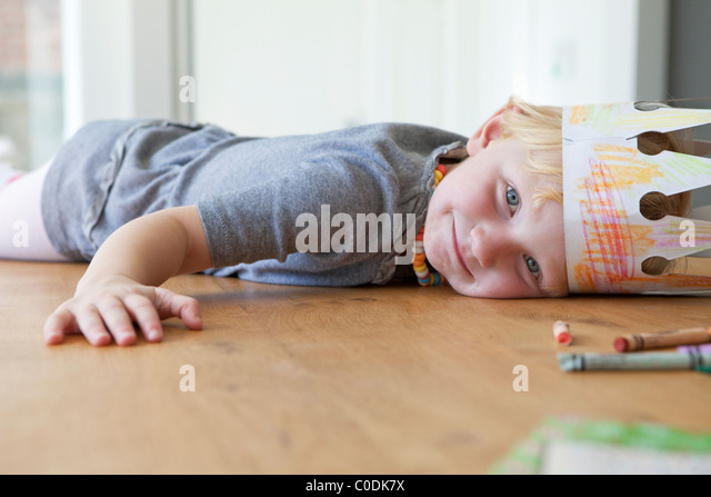 Little girl laying on wooden table - Stock Image
