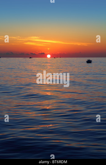 seascape sunrise first sun orange in blue sea ocean - Stock Image