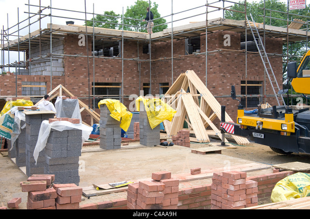 View of a new house in the process of being built ,at the stage just before roof trusses are added. - Stock Image