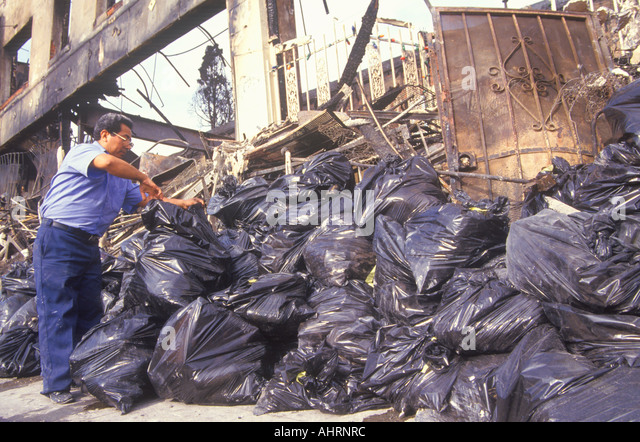 Man piling trash bags after 1992 riots South Central Los Angeles California - Stock Image