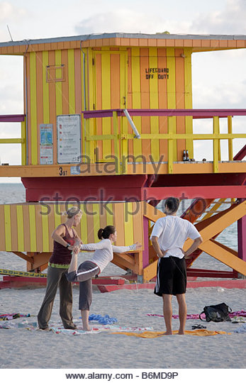 Miami Beach Florida yoga sand shore beach lifeguard stand woman women man exercise health fitness early morning - Stock Image