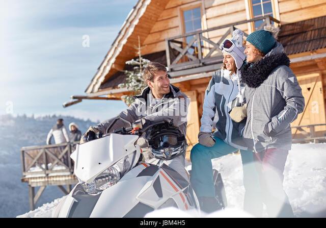 Friends with snowmobile outside sunny cabin - Stock-Bilder