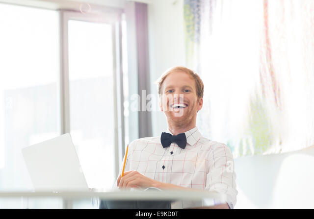Cheerful businessman sitting at desk in creative office - Stock Image