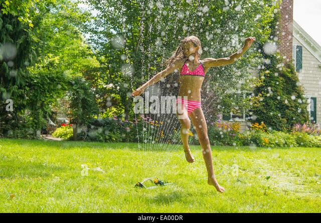 Girl in swimming costume jumping over garden sprinkler - Stock Image