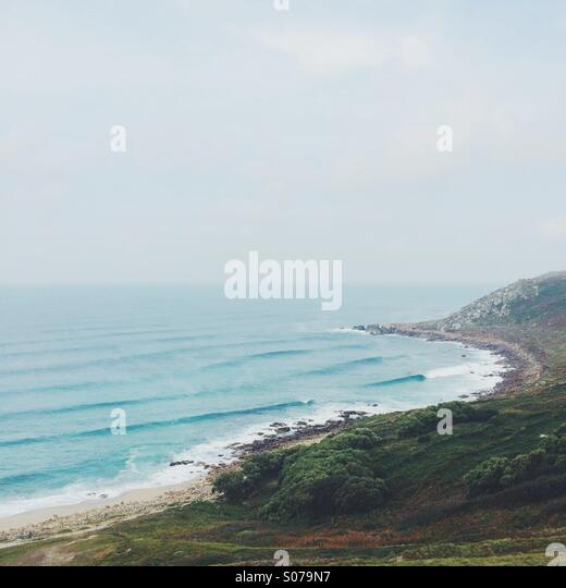 Waves rolling into a rocky shore and headland. - Stock Image