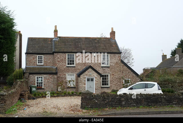 A small economic and environmentally friendly car outside a classic styled house in South Gloucestershire. 29th - Stock Image