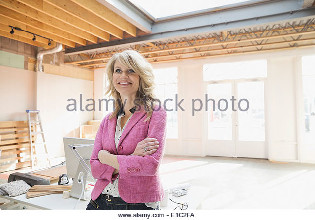 Smiling businesswoman in new office - Stock Image