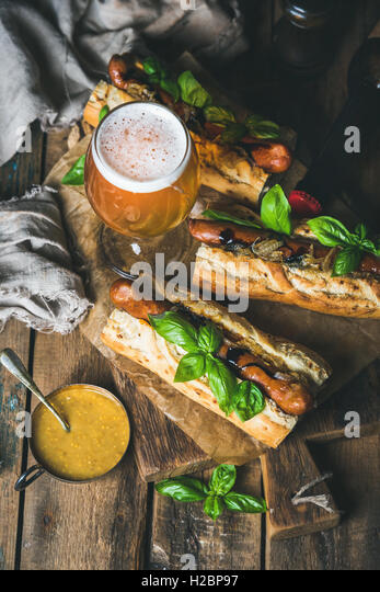 Glass and bottle of unfiltered beer, grilled sausage dogs - Stock Image