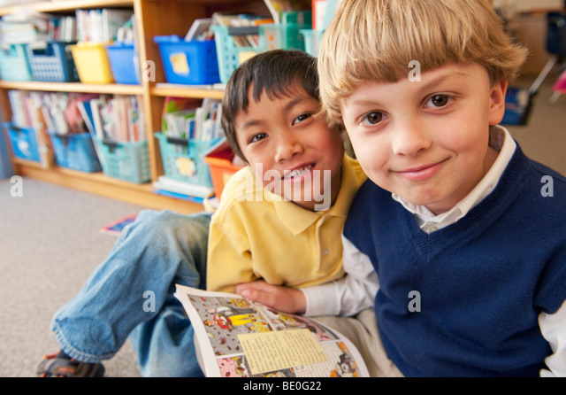 Students reading book together - Stock-Bilder