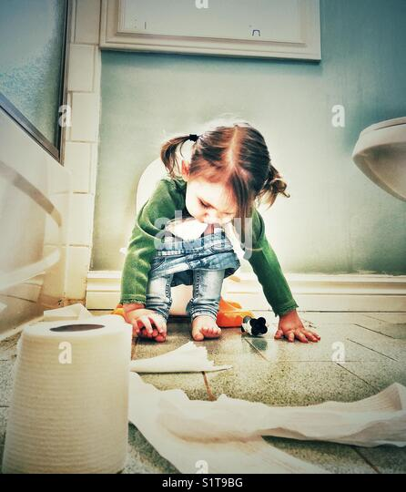 Lifestyle potty training image of toddler girl playing with toes while sitting on potty - Stock Image