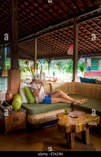 Woman relaxing with coffee and digital tablet in holiday apartment sitting room, Ubud, Bali, Indonesia - Stock Image