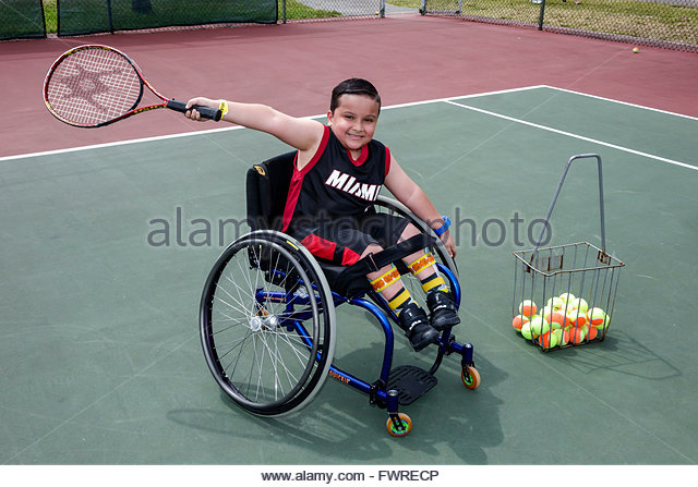 Florida FL Miami Tropical Park Paralympic Experience sports disabled tennis court wheelchair Hispanic boy racket - Stock Image