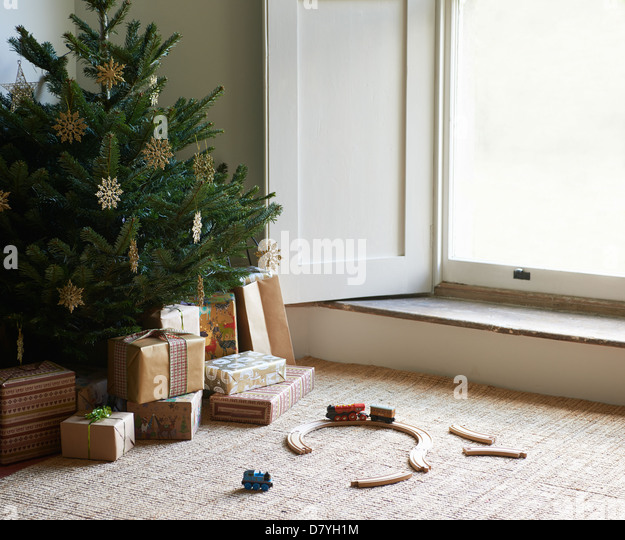 Train set and Christmas gifts under tree - Stock Image
