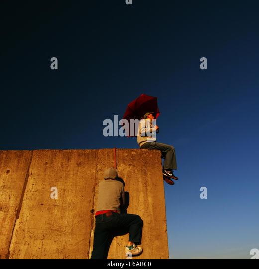 humor,bizarre,wall,climbing,umbrella - Stock Image