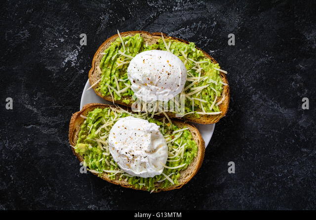Two toasts with mashed avocado, cheese and poached egg on dark textured backdrop, top view. Healthy breakfast or - Stock Image