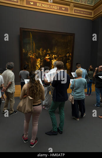 Tourists and visitors admire the Night Watch, by Rembrandt, 1642, Rijksmuseum, Amsterdam, Netherlands, Europe, - Stock Image