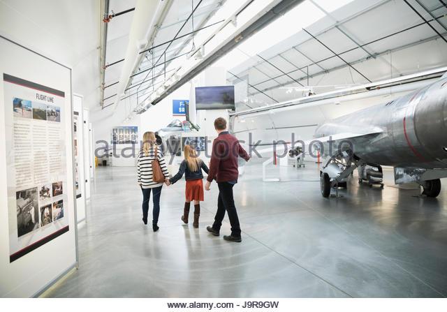 Family walking, looking at airplanes in war museum hangar - Stock-Bilder