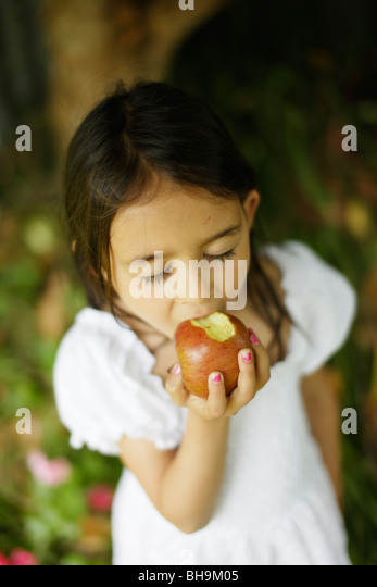 Six year old girl bites into apple - Stock Image