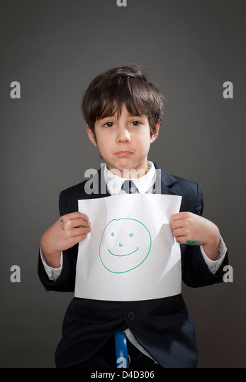 Sad boy with drawing of happy face - Stock Image