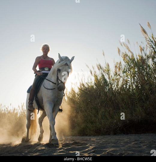 Woman riding horse on the beach - Stock Image
