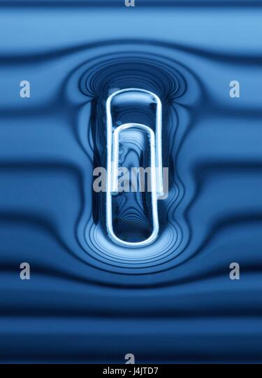 Paperclip floating on the water surface. - Stock Image