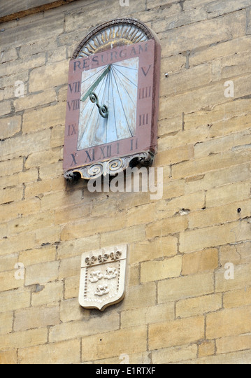 Sun dial with a picture of the sun rising and the word 'Resurgam', I shall rise again in Latin.  Cathedral - Stock Image