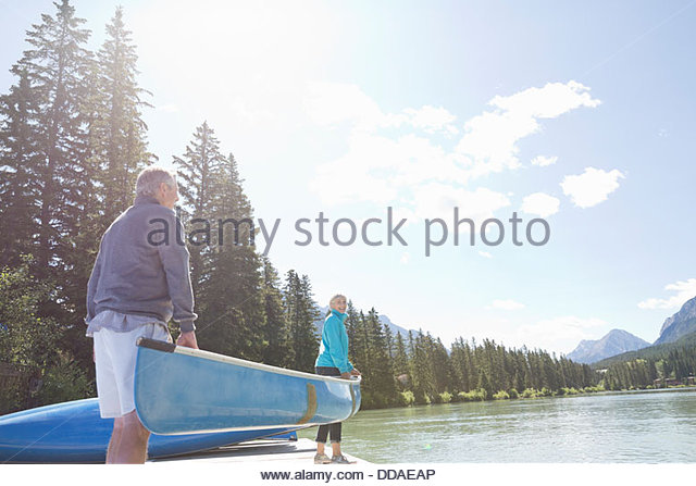 Couple carrying canoe to riverbank - Stock Image