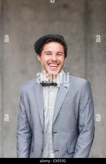 Young man wearing flat cap and bow tie, laughing - Stock Image