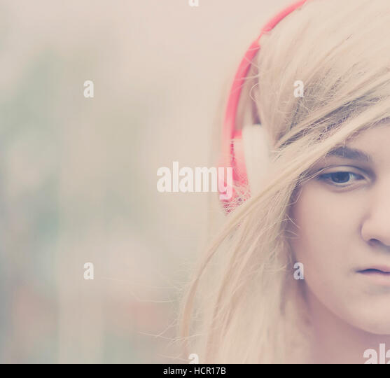 Girl listening to music on headphones - Stock Image