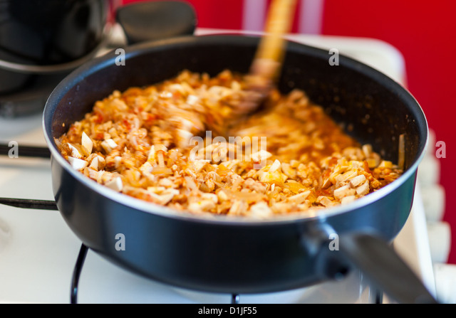 Closeup of stew cooking in pan while stirring with wooden spoon - Stock Image