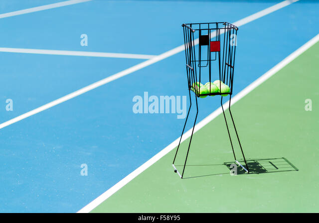 Beautiful tennis court with a ball basket and tennis balls in it - Stock Image