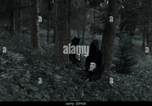 People wearing black robes and holding white masks sitting in forest - Stock Image