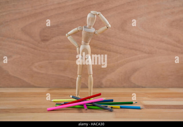 Wooden figurine selecting colour pencil - Stock Image